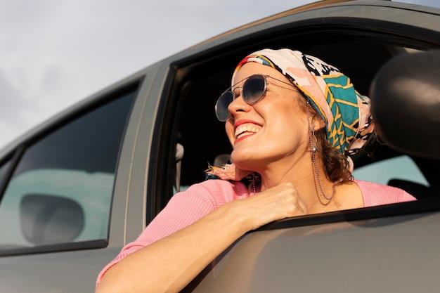 Mulher sorridente viajando de carro