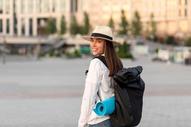 Mulher sorridente viajando sozinha com mochila