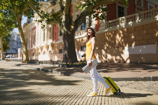 Mulher sorridente viajante turista em roupas casuais de verão amarelo, chapéu com mapa da cidade mala andar na cidade ao ar livre. garota viajando para o exterior para viajar na escapadela de fins de semana. conceito de estilo de vida de viagem de turismo.