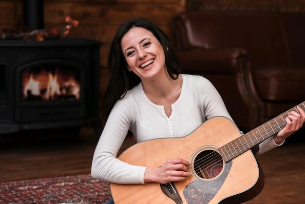 Mulher sorridente, violão jogo