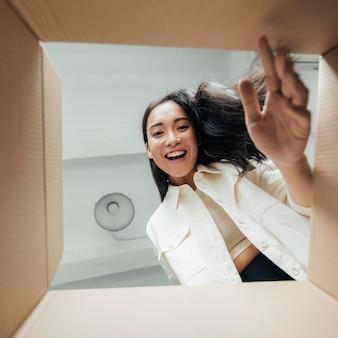 Mulher sorridente, vista de baixo, olhando para uma caixa