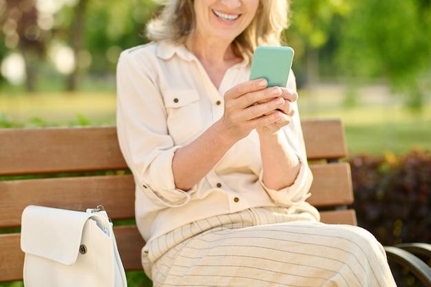 Mulher sorrindo alegremente com smartphone nas mãos