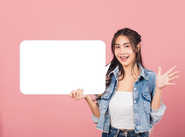 Mulher sorrindo, animada, vestir jeans segurando um cartaz de balão vazio