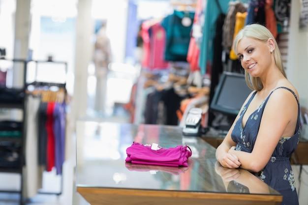 Mulher sorrindo atrás do balcão com roupas dobradas