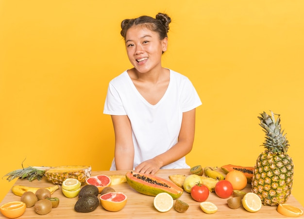 Mulher, sorrindo, câmera, atrás de, um, tabela, com, frutas