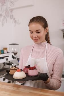 Mulher sorrindo, carregando sobremesas em um prato, trabalhando em sua cafeteria