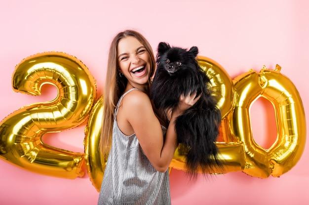 Mulher sorrindo com cachorro preto spitz japonês e balões de ano novo em 2020 dourado isolados sobre rosa