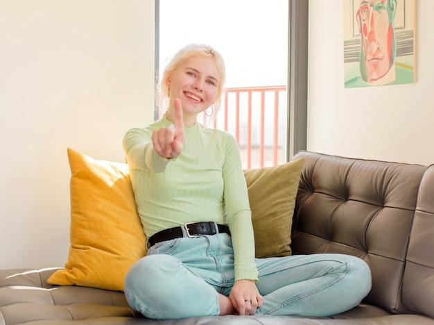 Mulher sorrindo com orgulho e confiança fazendo a pose número um triunfantemente, mulher se sentindo uma líder