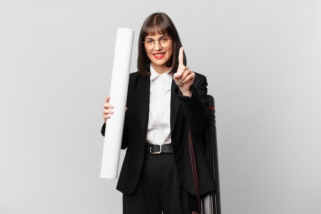 Mulher sorrindo com orgulho e confiança fazendo a pose número um triunfantemente, sentindo-se uma líder