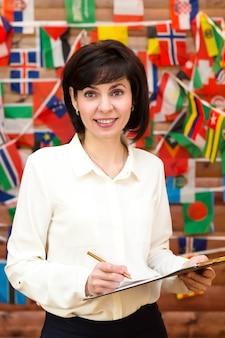 Mulher sorrindo com sucesso negociando internacionalmente. parede de bandeiras do mundo