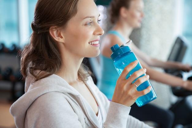 Mulher sorrindo com uma garrafa de água