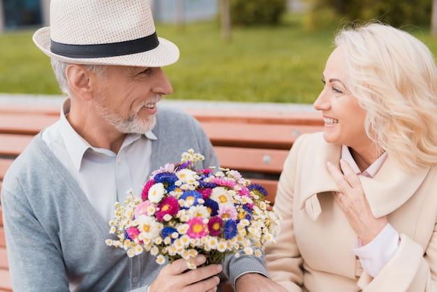 Mulher sorrindo. dois pensionistas sentam-se no banco.