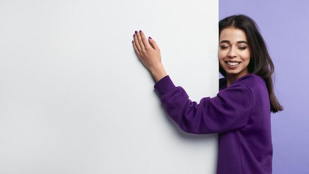 Mulher sorrindo e abraçando um banner vertical em branco com os olhos fechados