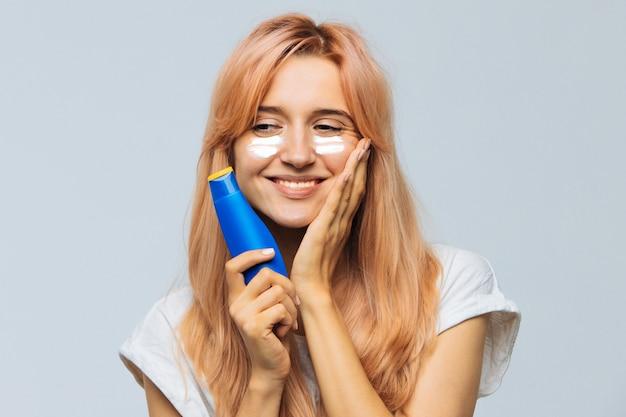 Mulher sorrindo e aplicando creme bronzeador (loção protetor solar) no rosto, bochechas com creme de proteção solar. queimadura de sol