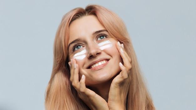 Mulher sorrindo e aplicando creme bronzeador