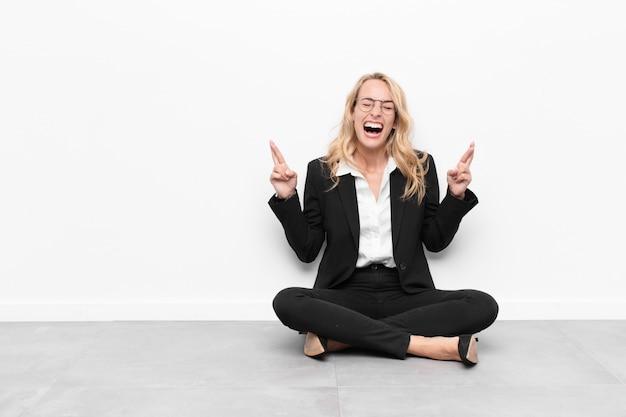Mulher sorrindo e cruzando ansiosamente os dois dedos, sentindo-se preocupada e desejando ou esperando boa sorte