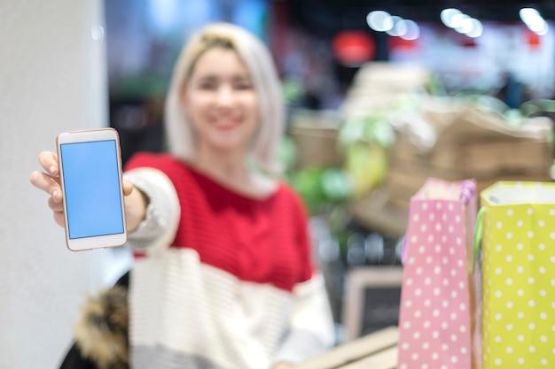 Mulher sorrindo e mostrando a tela em branco do seu celular
