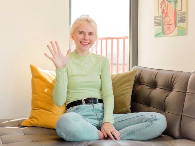 Mulher sorrindo e mulher parecendo amigável, mostrando o número cinco ou quinto com a mão para a frente, em contagem regressiva
