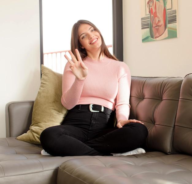 Mulher sorrindo e mulher parecendo amigável, mostrando o número três ou terceiro com a mão para a frente, em contagem regressiva