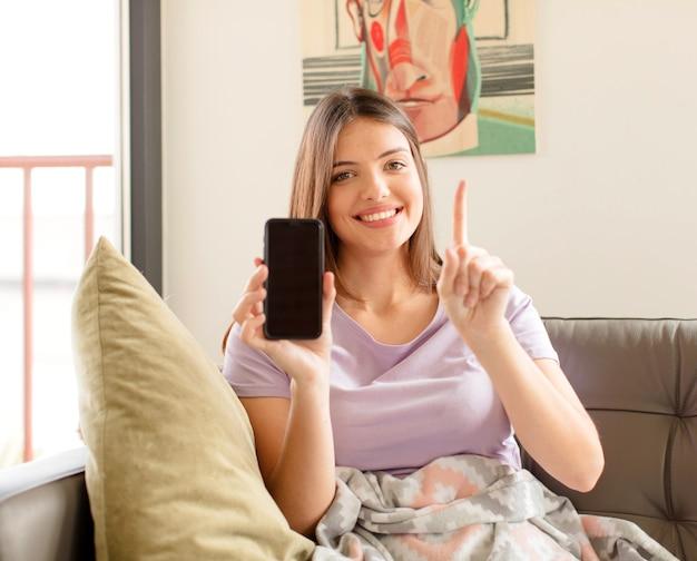 Mulher sorrindo e mulher parecendo amigável, mostrando o número um ou primeiro com a mão para a frente, em contagem regressiva