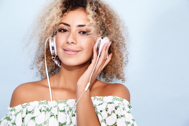 Mulher sorrindo e ouvindo música em fones de ouvido