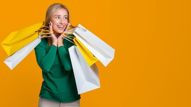 Mulher sorrindo e posando com muitas sacolas de compras