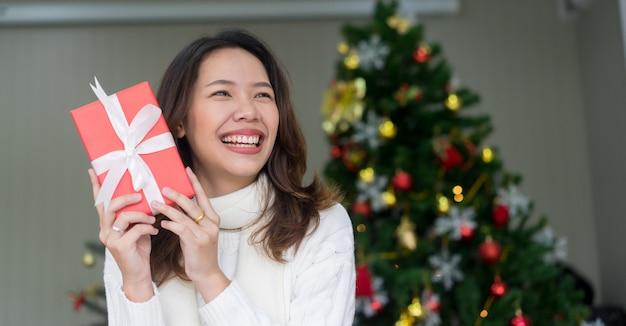Mulher sorrindo e segurando a caixa de presente vermelha na sala de estar em casa