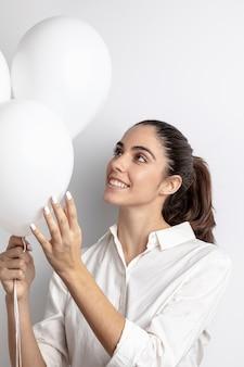Mulher sorrindo e segurando balões