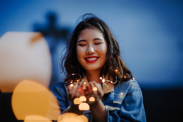 Mulher sorrindo e segurando luzes de corda à noite