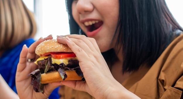Mulher sorrindo e segurando o hambúrguer