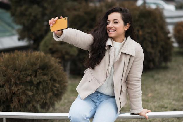Mulher sorrindo e tomando selfie ao ar livre