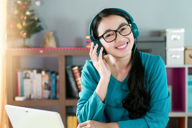 Mulher sorrindo e usando fones de ouvido para ouvir música ou conversar com videochamada