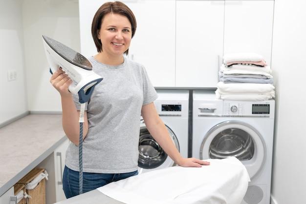 Mulher sorrindo em pé perto da tábua de passar roupa na lavanderia com máquina de lavar