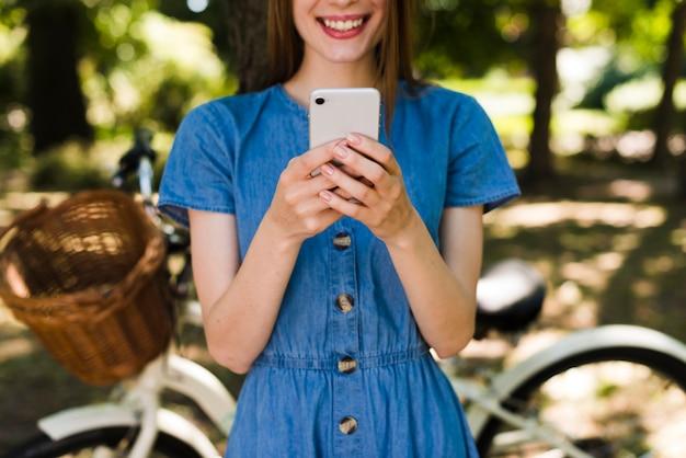 Mulher, sorrindo, em, telefone, com, defocused, bicicleta