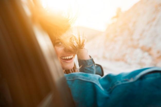 Mulher sorrindo enquanto estiver em um passeio de carro