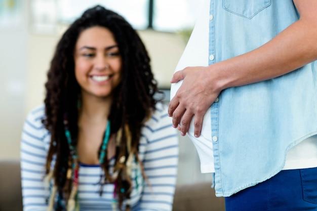 Mulher sorrindo enquanto olha para a barriga de parceiros grávidas