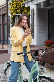Mulher sorrindo enquanto olha para o smartphone e está sentada na bicicleta