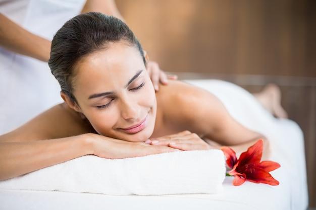 Mulher sorrindo enquanto recebe massagem