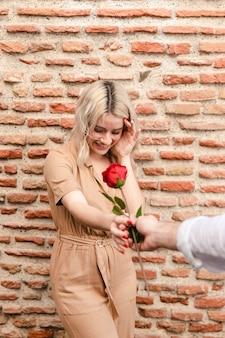 Mulher sorrindo enquanto recebe uma rosa