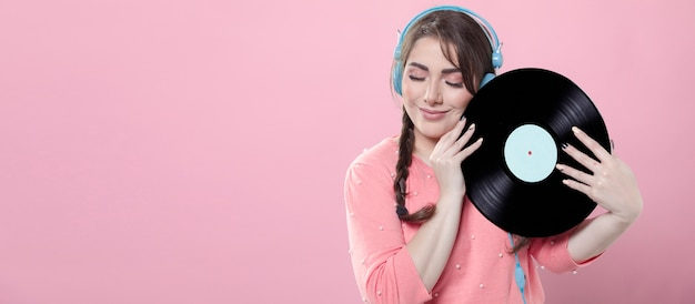 Mulher sorrindo enquanto segura o disco de vinil e usando fones de ouvido
