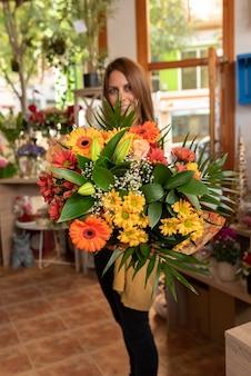 Mulher sorrindo, entregando buquê de flores