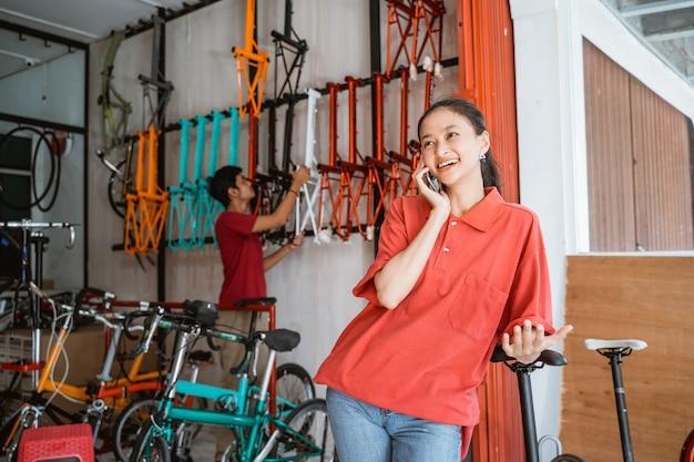 Mulher sorrindo feliz enquanto conversa usando um telefone celular em uma loja de bicicletas