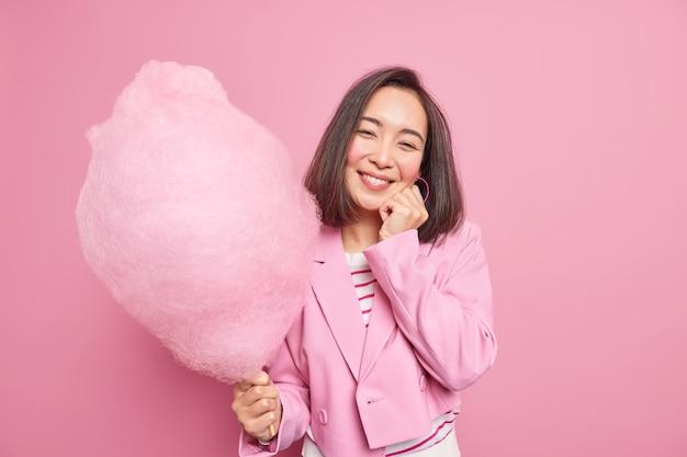 Mulher sorrindo gentilmente segurando o rosto segurando algodão doce no palito e vestindo roupas formais