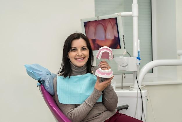 Mulher sorrindo na odontologia com modelo de mandíbula