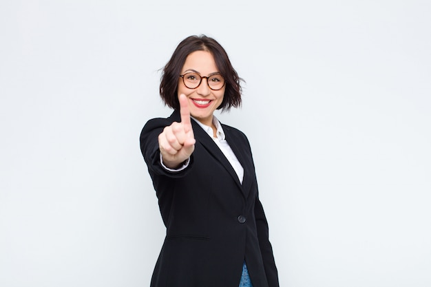 Mulher sorrindo orgulhosa e confiante fazendo pose número um triunfante, sentindo-se como um líder