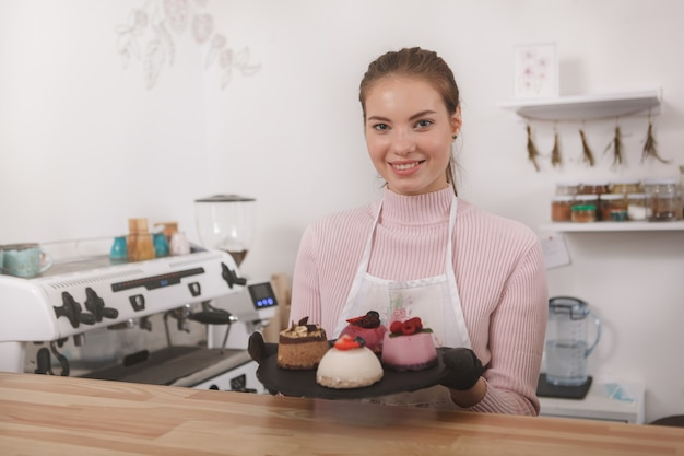 Mulher sorrindo para a câmera, servindo deliciosas sobremesas em sua cafeteria