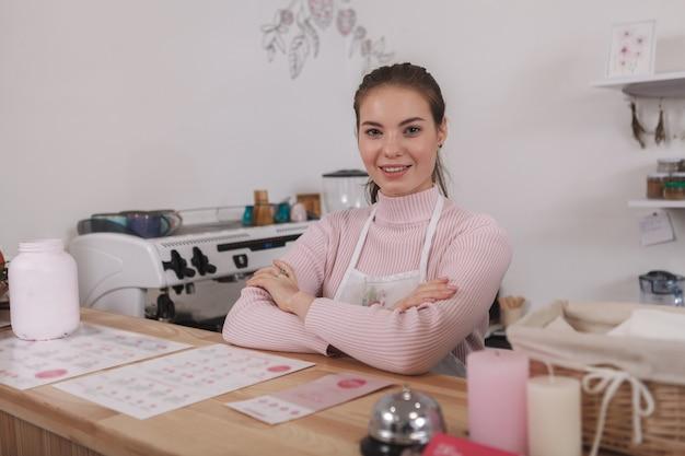 Mulher sorrindo para a câmera trabalhando em sua cafeteria