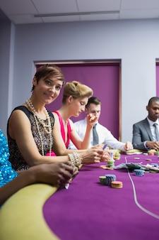 Mulher sorrindo para o casino sentado na mesa de poker