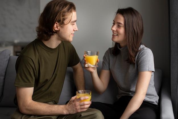 Mulher sorrindo para o namorado, segurando o copo de suco de laranja
