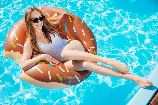 Mulher, sorrindo, posar, donut, nadar, anel